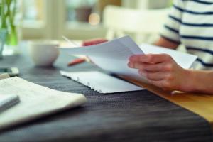 frau sitzt am kchentisch und liest einen brief