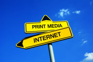 Print Media or Internet - Traffic sign with two options - dilemma between anachronism and modern way of publishing. Magazines and newspapers vs online news, blogs and social media